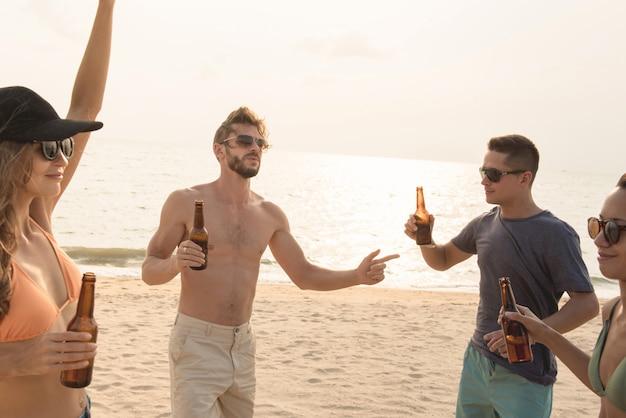 Grupo de amigos bebiendo en la playa Foto Premium