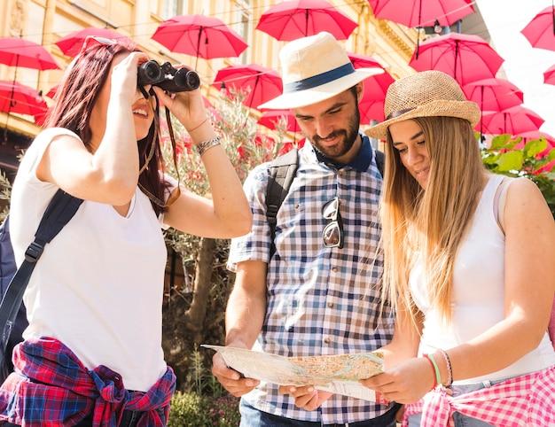 Grupo de amigos buscando localización a través de binoculares y mapa. Foto gratis