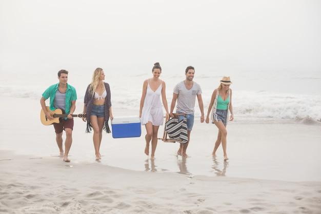 Grupo de amigos caminando por la playa Foto Premium