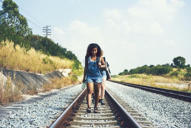 Grupo de amigos caminando por las vías del tren Foto Premium