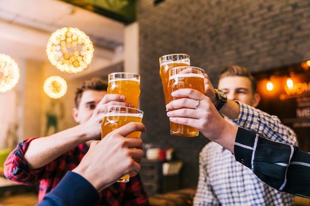 Grupo de amigos celebrando el éxito con vasos de cerveza. Foto gratis