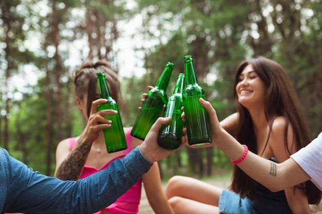 Grupo de amigos chocan botellas de cerveza durante el picnic en el bosque de verano Foto gratis