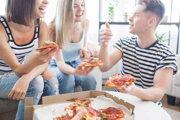 Grupo de amigos comiendo pizza en el interior Foto Premium