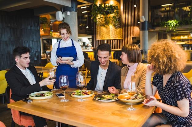 Grupo de amigos comiendo en restaurante Foto gratis