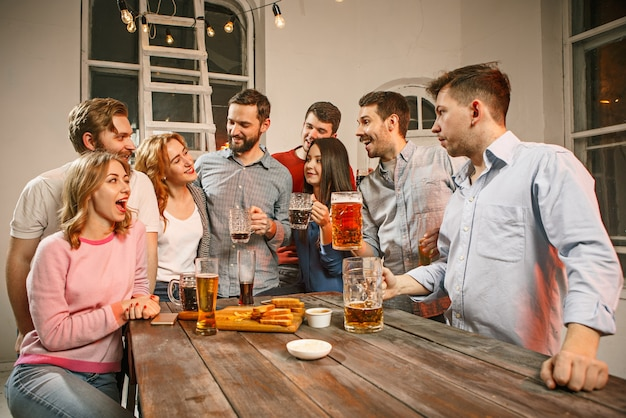 Grupo de amigos disfrutando de bebidas con cerveza por la noche Foto gratis