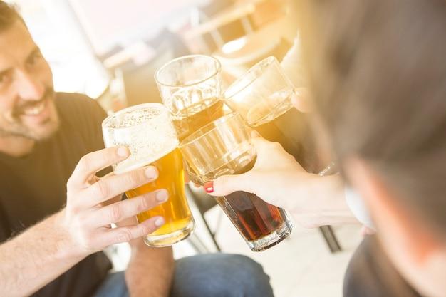 Grupo de amigos disfrutando de bebidas por la noche en el bar Foto gratis