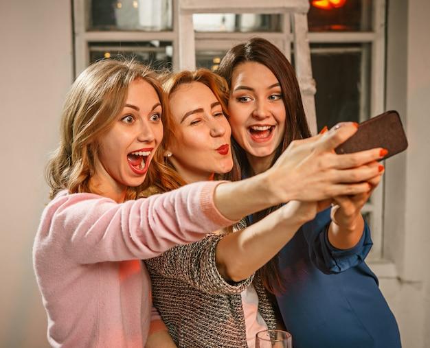 Grupo de amigos disfrutando de bebidas por la noche con cerveza y chicas haciendo selfie foto Foto gratis