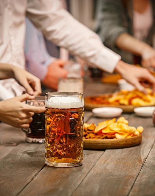 Grupo de amigos disfrutando de bebidas por la noche con cerveza en la mesa de madera Foto gratis