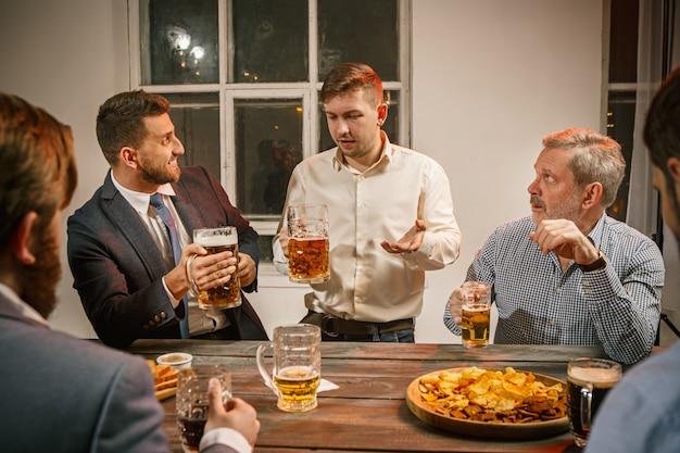 Grupo de amigos disfrutando de bebidas por la noche con cerveza Foto gratis