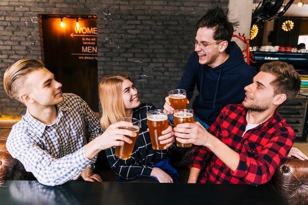 Grupo de amigos disfrutando de la cerveza en pub. Foto gratis