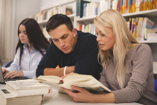 Grupo de amigos disfrutando de estudiar juntos en la biblioteca Foto Premium