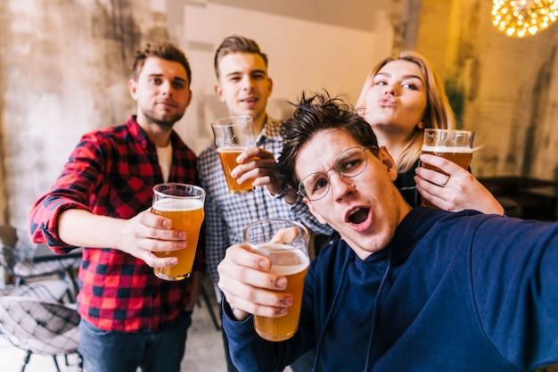 Grupo de amigos disfrutando de la selfie disfrutando de la cerveza en pub. Foto gratis