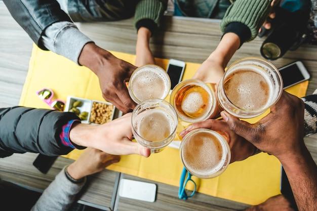 Grupo de amigos disfrutando de unos vasos de cerveza en el restaurante de pub inglés. jóvenes animando en bar vintage Foto Premium
