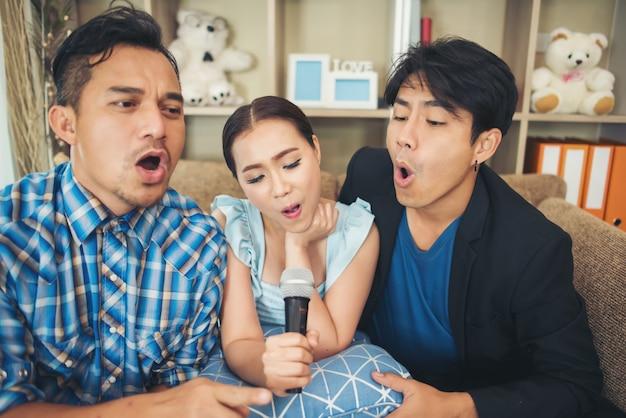 Grupo de amigos divirtiéndose en la sala de estar cantando una canción juntos Foto gratis