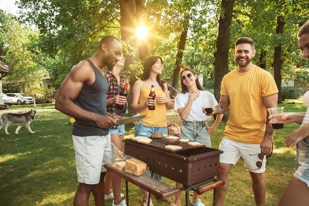 Grupo de amigos felices con cerveza y fiesta de barbacoa en un día soleado. descansar juntos al aire libre en un claro del bosque o en el patio trasero Foto gratis