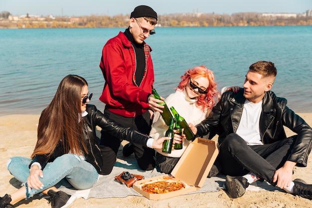 Grupo de amigos felices divirtiéndose y tintineando botellas en la playa Foto gratis