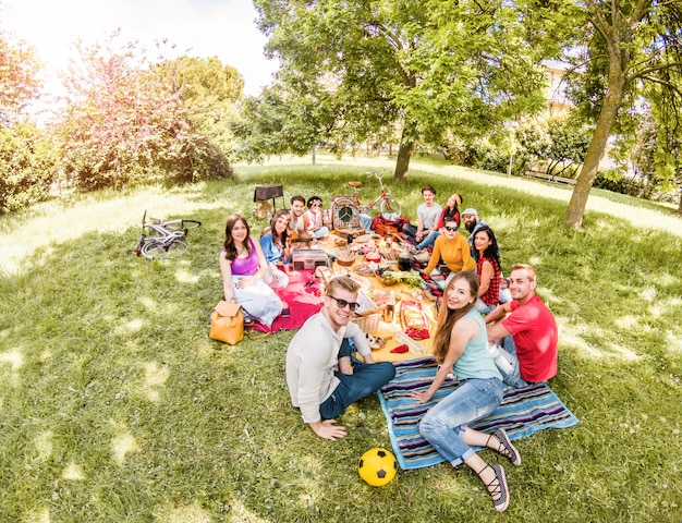 Grupo de amigos felices haciendo picnic en el parque público al aire libre - jóvenes bebiendo vino y riendo en la naturaleza Foto Premium