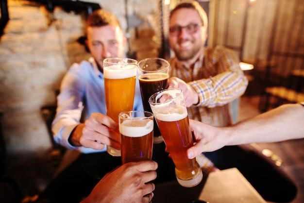Grupo de amigos haciendo un brindis en pub. Foto Premium