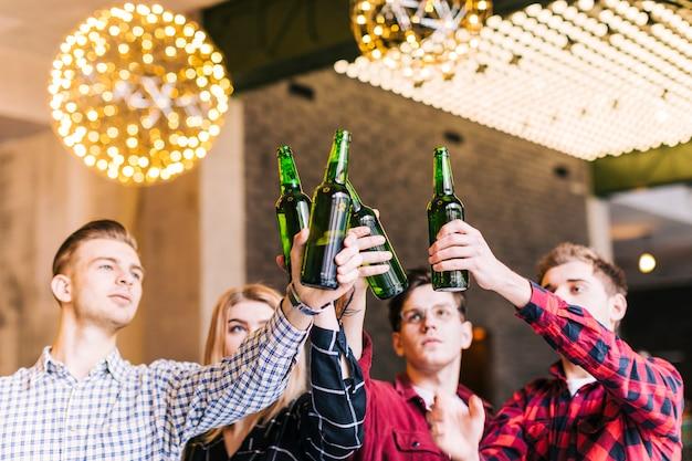 Grupo de amigos levantando las botellas de cerveza en restaurante pub Foto gratis