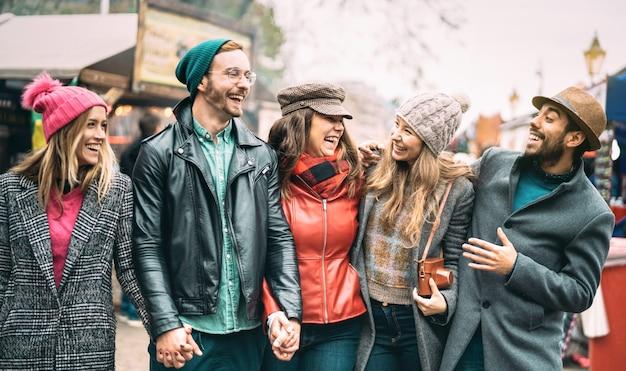 Grupo de amigos del milenio divirtiéndose juntos caminando en el centro de londres Foto Premium