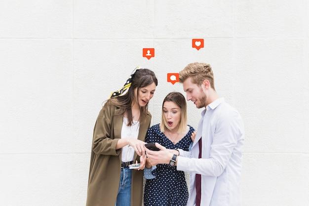 Grupo de amigos de pie cerca de la pared de mensajes de texto en el teléfono móvil Foto gratis