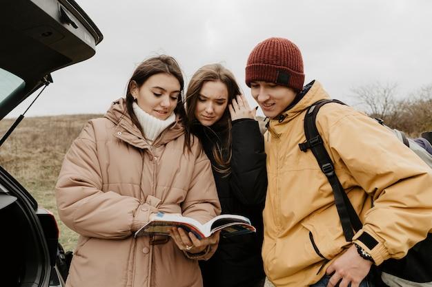 Grupo de amigos que consulta la guía Foto gratis