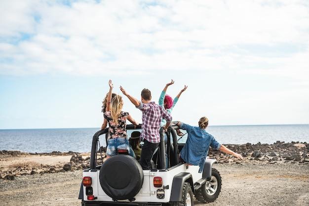 Grupo de amigos que hacen una excursión por el desierto con un auto 4x4 convertible - concepto de amistad, recorrido, juventud, estilo de vida y vacaciones - enfoque en los cuerpos de los chicos Foto Premium