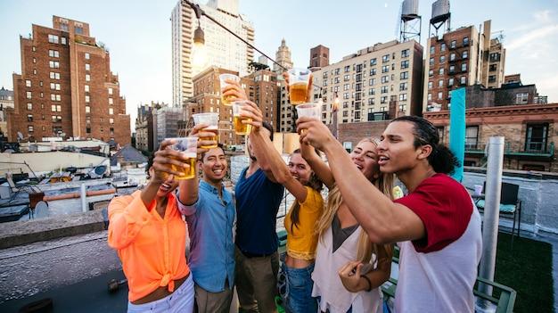 Grupo de amigos que pasan tiempo juntos en una azotea en la ciudad de nueva york, concepto de estilo de vida con gente feliz Foto Premium