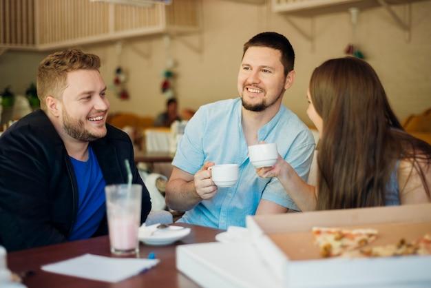 Grupo de amigos reunidos en pizzería Foto gratis