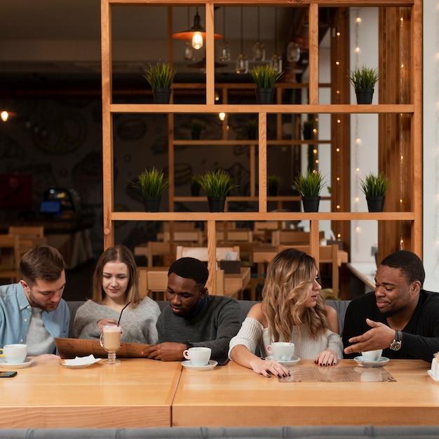 Grupo de amigos reunidos en el restaurante Foto gratis