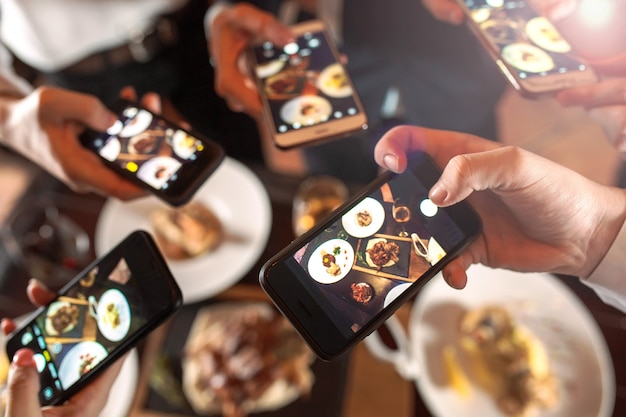 Grupo de amigos saliendo y tomando una foto de comida junto con un teléfono móvil. Foto Premium