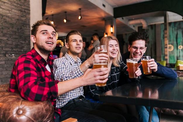 Grupo de amigos sentados en el bar restaurante disfrutando de la cerveza. Foto gratis