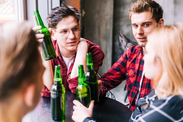 Grupo de amigos sentados juntos sosteniendo botellas de cerveza verde Foto gratis