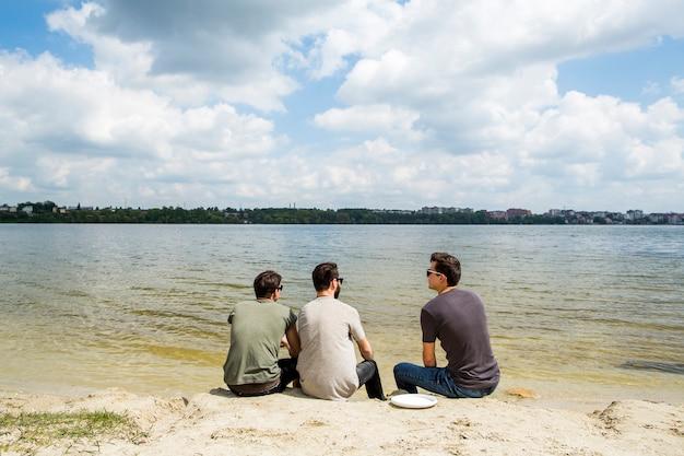Grupo de amigos sentados en la playa de arena Foto gratis