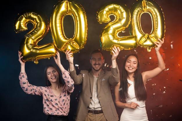 Grupo de amigos sosteniendo globos de año nuevo Foto gratis