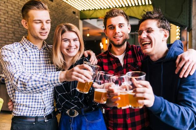 Grupo de amigos tintineando los vasos de cerveza en pub Foto gratis