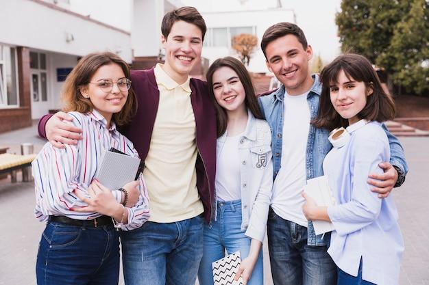 Grupo de amigos universitarios que abrazan Foto gratis