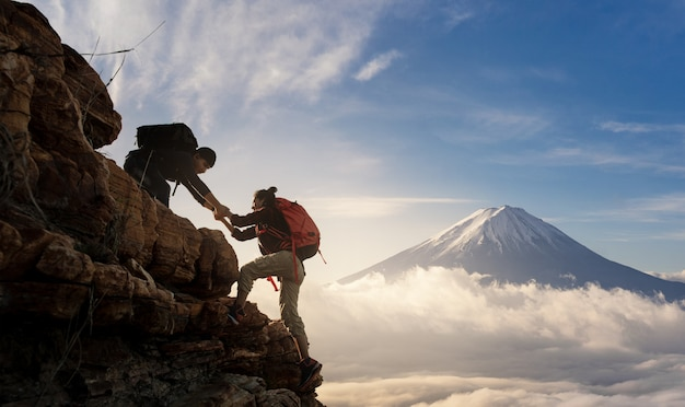 Grupo de asia senderismo ayudarse mutuamente silueta en las montañas con la luz solar. Foto Premium