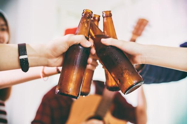 Grupo asiático de amigos de fiesta con bebidas de cerveza alcohólicas y jóvenes disfrutando en un bar a Foto Premium