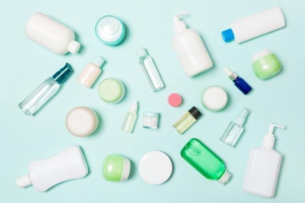 Grupo de botella de plástico para el cuidado del cuerpo composición plana con productos cosméticos en el espacio vacío azul para su diseño. conjunto de envases cosméticos blancos, vista superior con copyspace Foto Premium