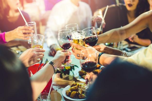 Grupo de chicas festejando tintineo de flautas con vino espumoso, amigo Foto Premium