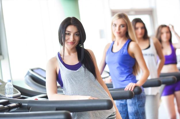 Un grupo de chicas guapas en buena forma corriendo en las cintas de correr. mujeres bonitas entrenando en el gimnasio. niña está sonriendo a la cámara Foto Premium
