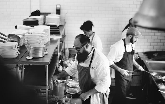 Grupo de cocineros que trabajan en la cocina. Foto gratis