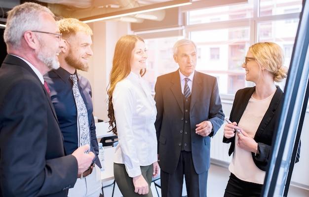 Grupo de colegas del negocio que miran a la empresaria joven que da la presentación Foto gratis