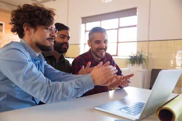Grupo de compañeros de trabajo viendo capacitación en línea o seminario web Foto gratis