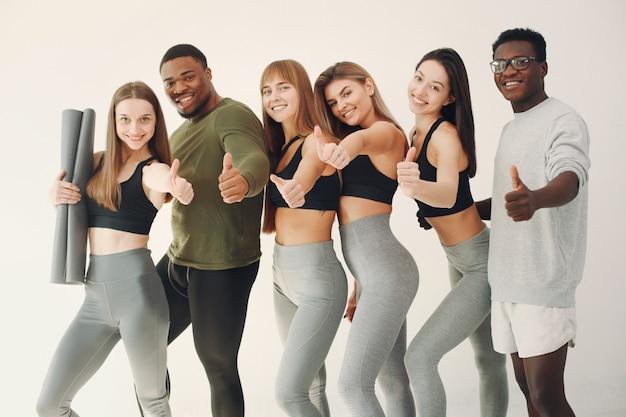 Grupo deportivo de pie sobre una pared blanca Foto gratis