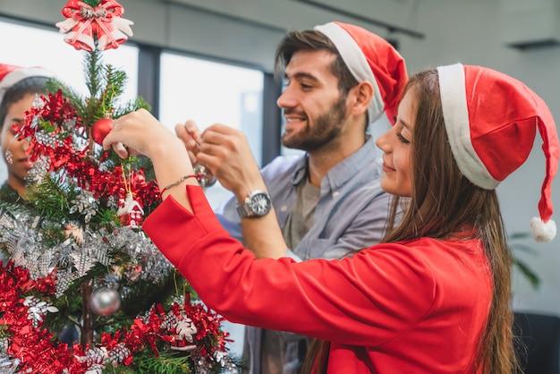 Grupo de diversidad joven creativo feliz celebrando feliz navidad y feliz año nuevo decorando el árbol de navidad en la oficina en la oficina moderna Foto Premium