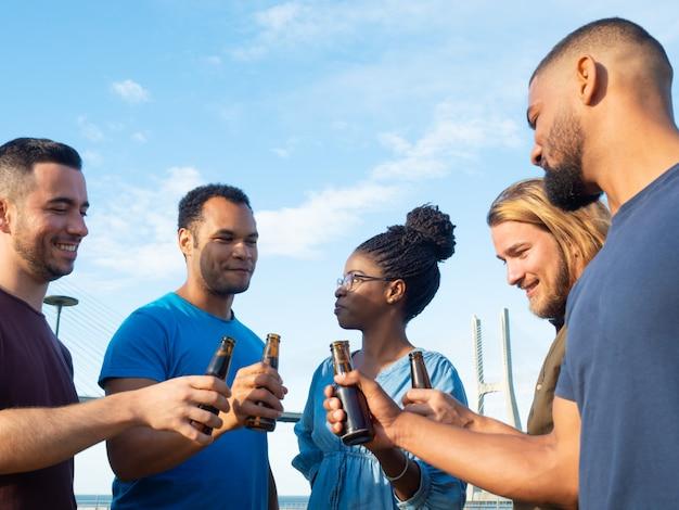 Grupo diverso de amigos bebiendo cerveza afuera Foto gratis