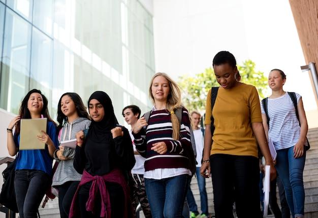 Grupo diverso de estudiantes caminando en la escuela. Foto gratis