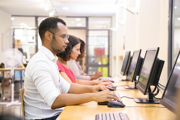 Grupo diverso de estudiantes que toman exámenes en línea. Foto gratis
